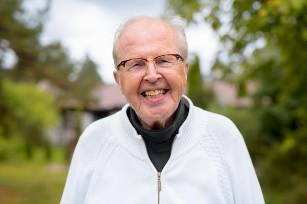 Porträt des älteren mannes, der brillen zu hause im freien trägt
