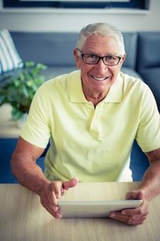 Porträt des älteren mannes, der digitale tablette verwendet