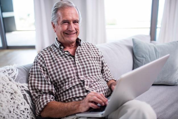 Porträt des älteren mannes, der laptop im wohnzimmer verwendet