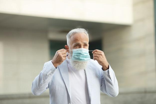 Porträt des älteren mannes, der medizinische maske trägt