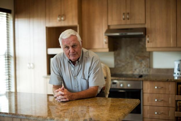 Porträt des älteren mannes, der mit den händen sitzt, die in der küche zu hause gefaltet werden