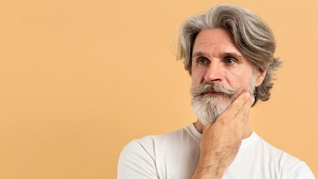 Porträt des älteren mannes, der mit kopierraum denkt