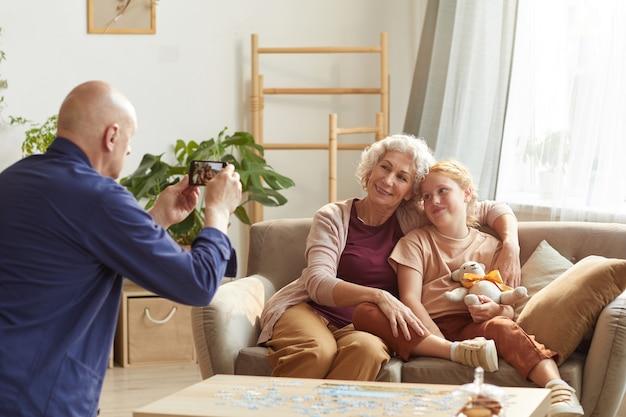 Porträt des älteren mannes, der smartphonefoto von frau und enkelin für familienerinnerungen macht