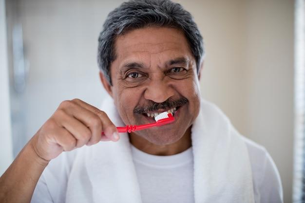 Porträt des älteren mannes, der zähne im badezimmer putzt