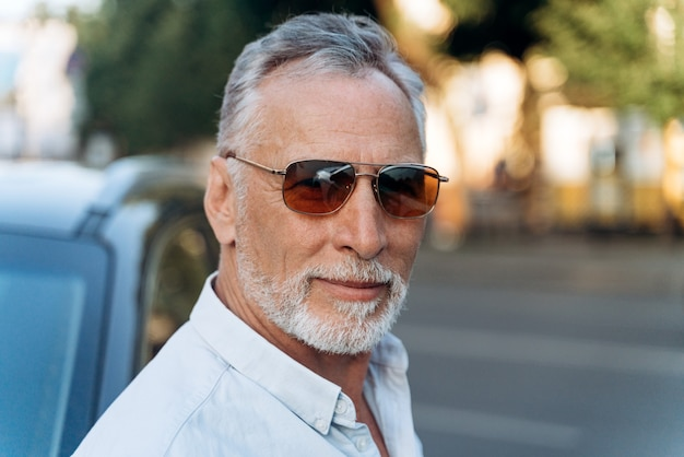 Porträt des älteren mannes im freien in einem hemd und in einer sonnenbrille
