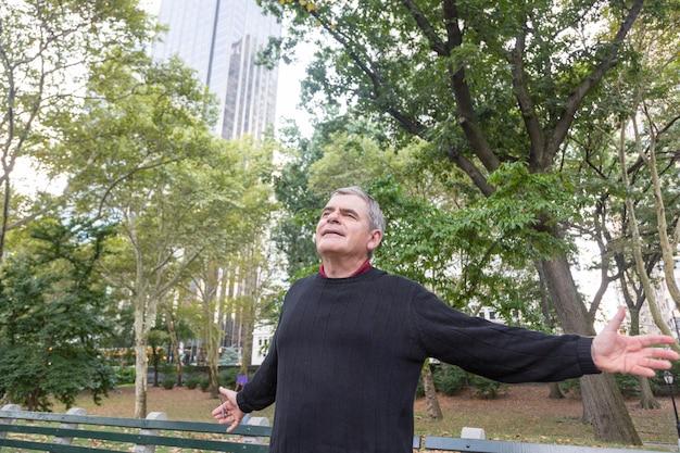 Porträt des älteren mannes im ruhestand am park, freiheitsgefühle