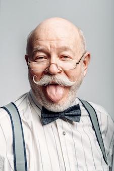 Porträt des älteren mannes in einer fliege und in den gläsern, die seine zunge auf grau zeigen. reifer senior, der kamera im studio betrachtet