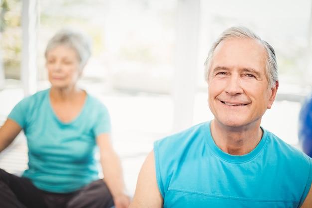Porträt des älteren mannes lächelnd mit der meditierenden frau