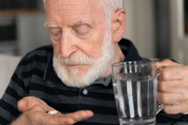 Porträt des älteren mannes mit alzeihmer drinnen
