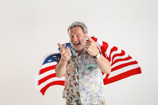 Porträt des älteren mannes mit flagge der vereinigten staaten von amerika lokalisiert auf weißem studio