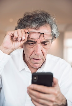 Porträt des älteren mannes smartphone betrachtend
