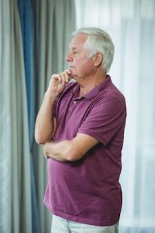Porträt des älteren mannes stehend mit der hand auf kinn