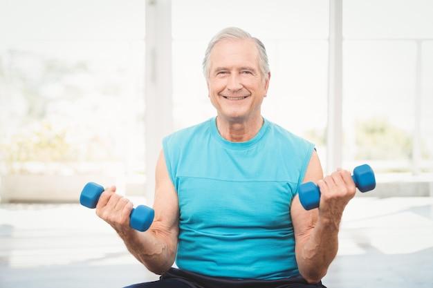 Porträt des älteren mannes trainierend mit dummköpfen
