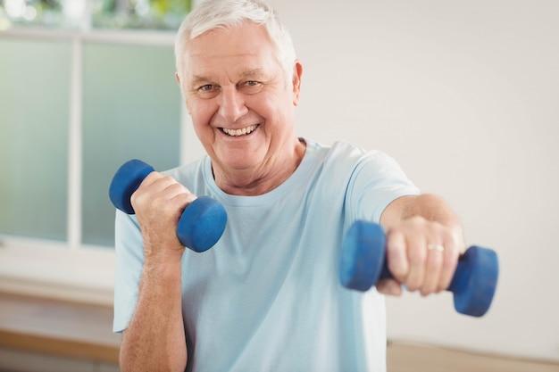 Porträt des älteren mannes zu hause trainierend mit dummköpfen