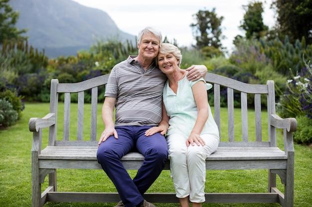 Porträt des älteren paares, das auf bank sitzt