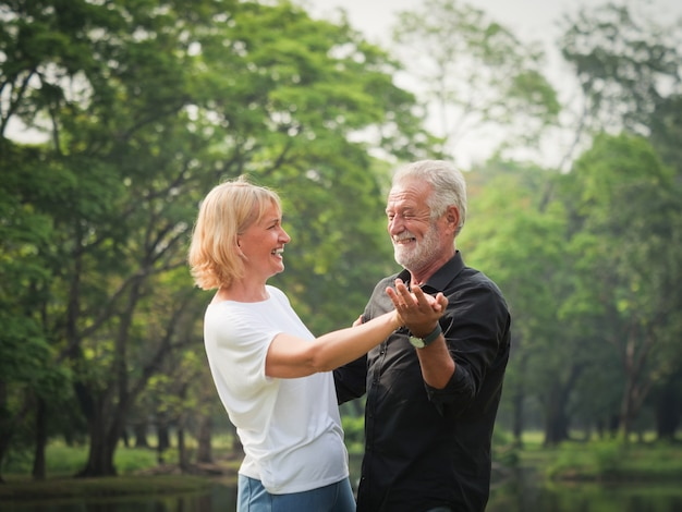 Porträt des älteren paarruhestands mann und frau, die zusammen im park tanzen