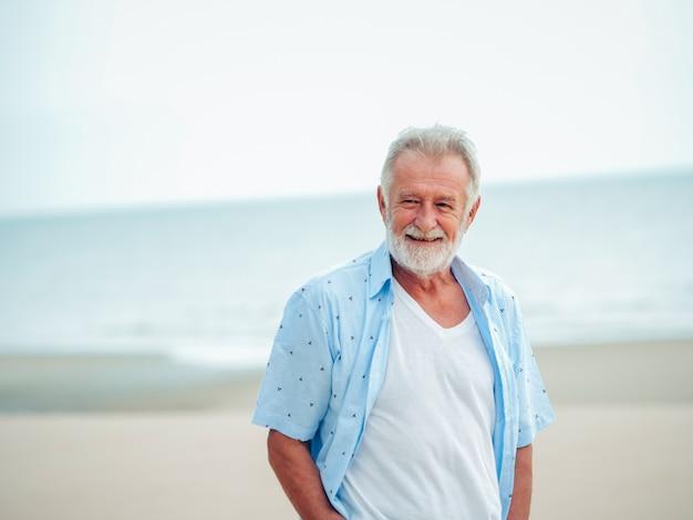 Porträt des älteren ruhestandsmannes auf dem strand