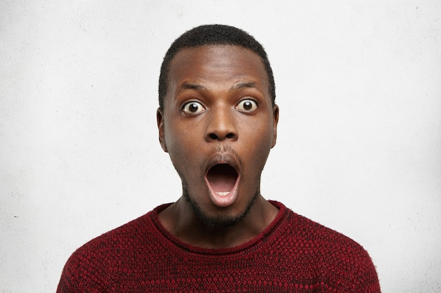 Porträt des ängstlichen jungen afroamerikanischen mannes mit bug-eyed im lässigen pullover, der vor schock schreit
