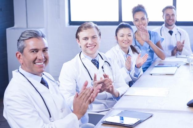 Porträt des ärzteteams applaudierend und im treffen am konferenzsaal lächelnd
