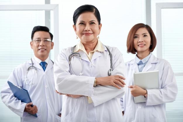 Porträt des ärzteteams von drei stehend im krankenhaus, das kamera betrachtet