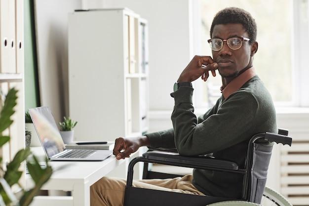 Porträt des afrikanischen behinderten mannes, der im rollstuhl sitzt, den er online auf laptop zu hause arbeitet