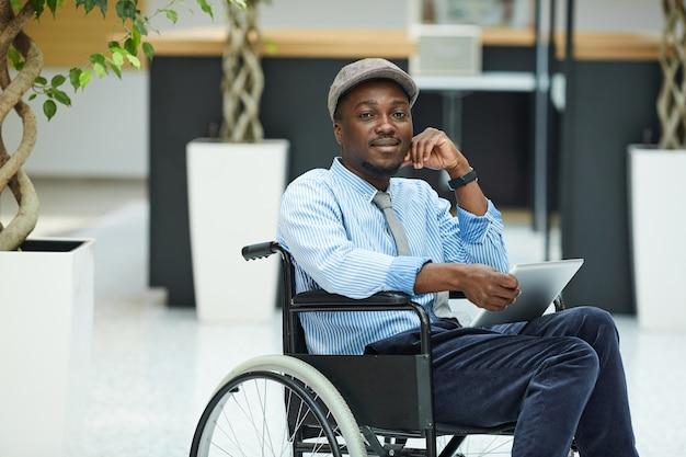 Porträt des afrikanischen behinderten mannes, der im rollstuhl sitzt und digitales tablett verwendet