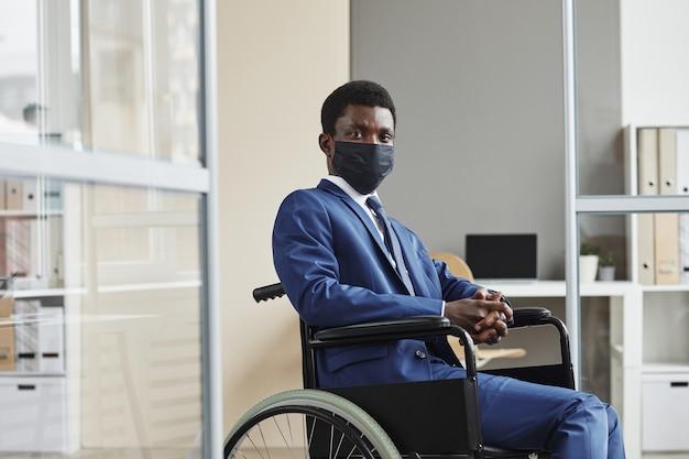 Porträt des afrikanischen behinderten mannes in der schutzmaske, die auf rollstuhl und im büro sitzt