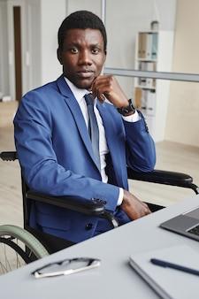 Porträt des afrikanischen geschäftsmannes im anzug, der im rollstuhl am büro sitzt