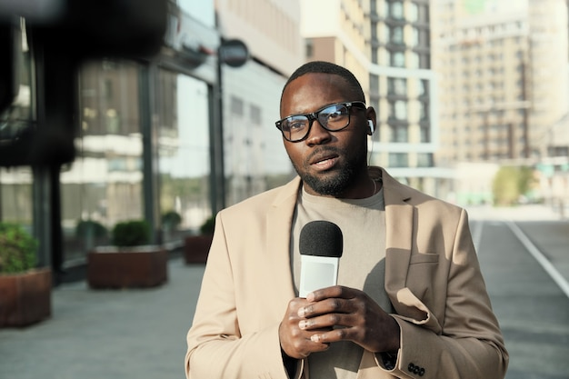 Porträt des afrikanischen journalisten in der brille, die im mikrofon während der arbeit in der stadt spricht