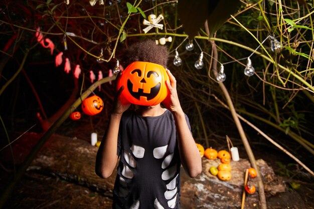 Porträt des afrikanischen jungen, der spielzeugkürbis vor seinem gesicht hält, das spaß an der halloween-party im dunkeln hat