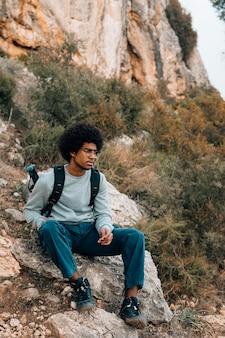 Porträt des afrikanischen jungen mannes, der auf berg sitzt