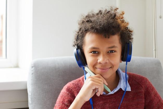 Porträt des afrikanischen jungen mit dem lockigen haar in den kopfhörern, die musik hören und lächeln