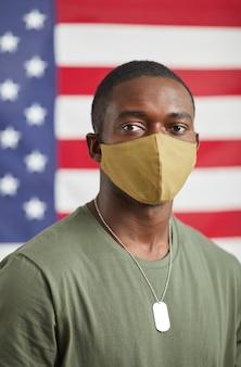 Porträt des afrikanischen jungen soldaten in der schutzmaske, die kamera betrachtet, die gegen die amerikanische flagge steht