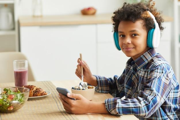 Porträt des afrikanischen kleinen jungen in den kopfhörern, die müsli essen und schauen, während sie online auf dem handy studieren