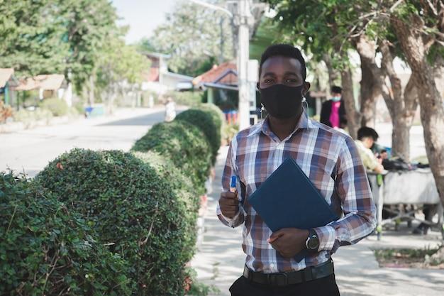 Porträt des afrikanischen lehrers in der gesichtsmaske, die draußen in der schule steht