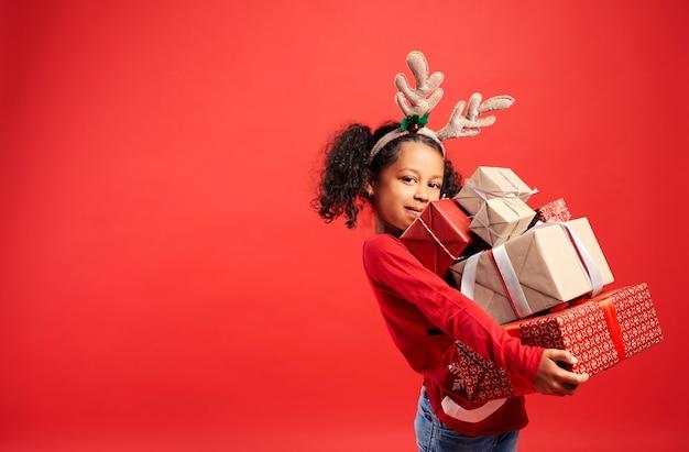 Porträt des afrikanischen mädchens, das stapel weihnachtsgeschenke trägt