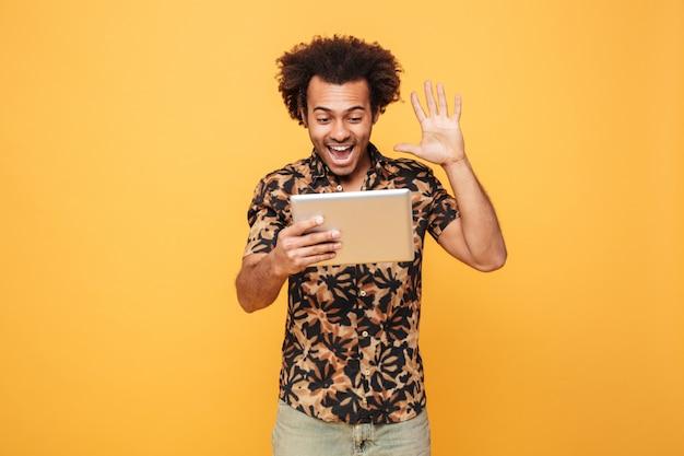 Porträt des afrikanischen mannes, der videoanruf durch pc-tablette hat