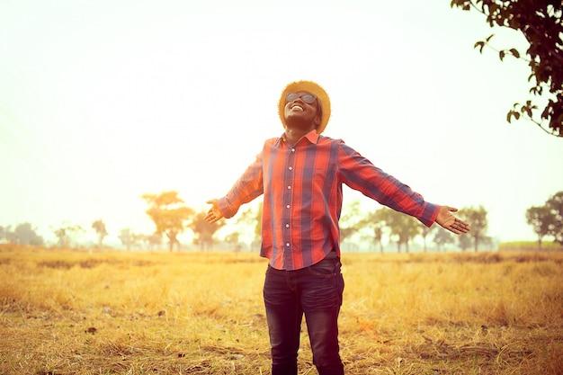 Porträt des afrikanischen reisenden lächelnd und seine erholungszeit in der natur genießend konzept des tourismus-tages