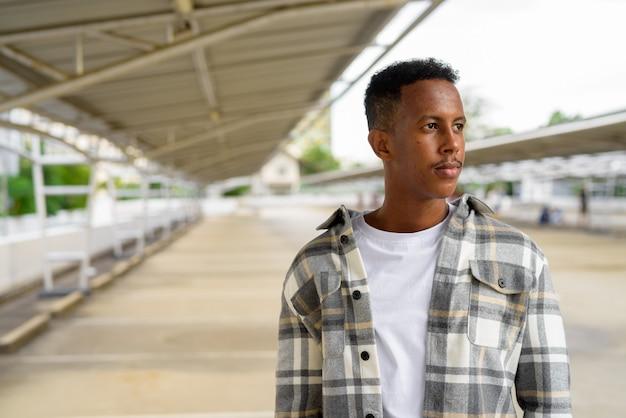 Porträt des afrikanischen schwarzen mannes, der während des horizontalen sommerschusses draußen in der stadt denkt