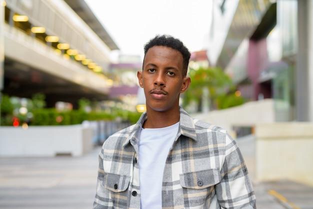 Porträt des afrikanischen schwarzen mannes draußen in der stadt während des horizontalen schusses des sommers