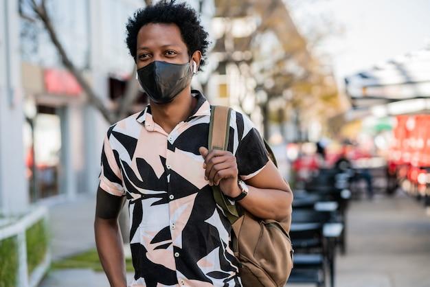 Porträt des afro-touristenmannes, der schutzmaske trägt, während draußen auf der straße steht