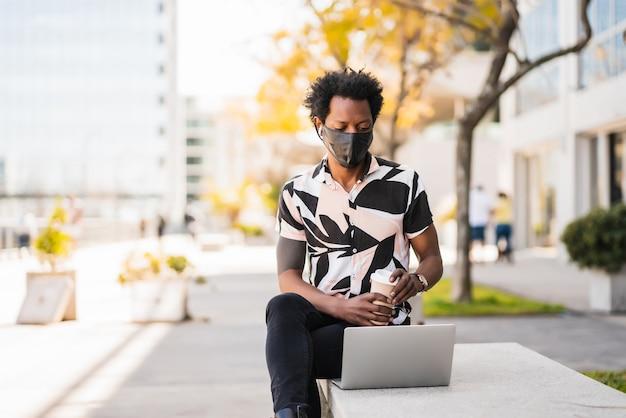 Porträt des afro-touristenmannes, der seinen laptop benutzt und schutzmaske trägt, während draußen sitzt. neues normales lifestyle-konzept.