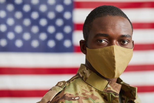 Porträt des afroamerikanermannes in der schutzmaske, die kamera betrachtet, die gegen die amerikanische flagge steht
