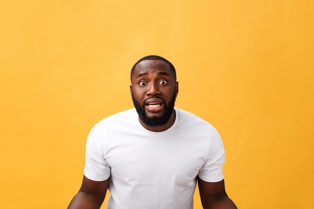 Porträt des afroamerikanermannes mit den händen hob in schock und in unglauben an. über gelbem hintergrund isoliert.