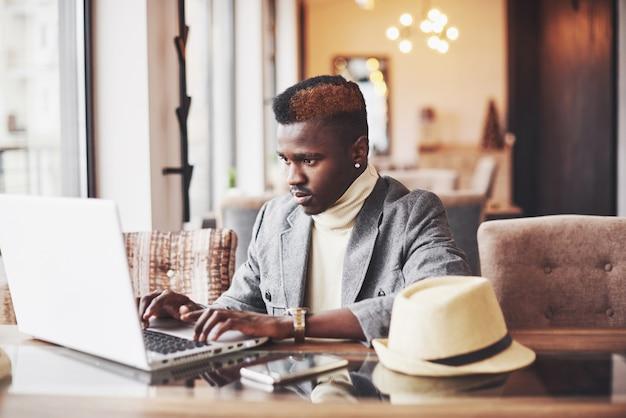 Porträt des afroamerikanermannes sitzend an einem café und an einem laptop arbeitend