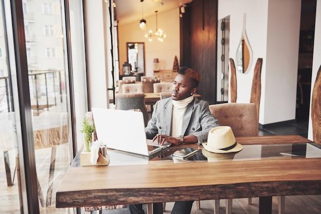 Porträt des afroamerikanermanns, der an einem café sitzt und an einem laptop arbeitet