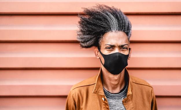 Porträt des afroamerikaners, der schwarze schützende gesichtsmaske trägt