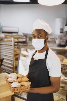 Porträt des afroamerikanischen bäckers mit frischem brot in der bäckerei. konditor, der kleines gebäck hält.