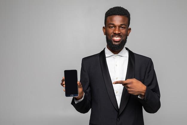 Porträt des afroamerikanischen geschäftsmannes. junger stilvoller geschäftsmann, der auf handy zeigt und lächelt. mann, der anzug und krawatte trägt