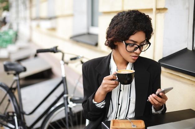 Porträt des afroamerikanischen mädchens in den gläsern, die am tisch des cafés mit handy und tasse kaffee in den händen sitzen